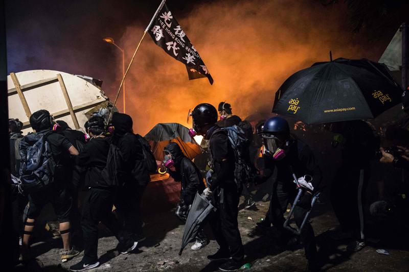 香港中文大學「反送中」學生12日持續在校園周邊與警方對峙,警方向學生發射催淚彈,學生向警方丟汽油彈。(Getty Images)