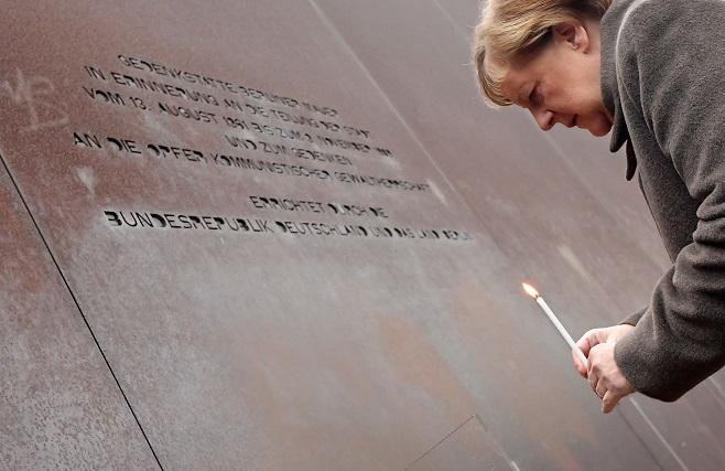 德國總理梅克爾9日點蠟燭紀念試圖翻越柏林圍牆被殺的民眾。(Getty Images)