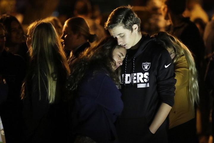 加州聖塔克拉利塔(Santa Clarita)的索格斯高中(Saugus High School)高中槍擊案發生後當晚,學生互相依偎守夜。(美聯社)
