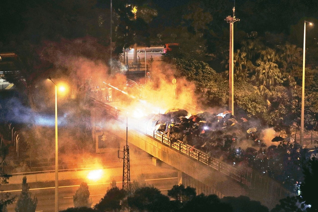 戴防毒面具的抗議者12日在香港中文大學外頭與警方對峙,抗議群眾夜間在橋上和鎮暴警察爆發衝突。 美聯社