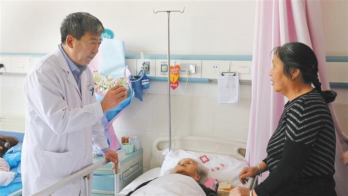 許向東(左)向病人家屬講述治療情況。圖取自陝西日報