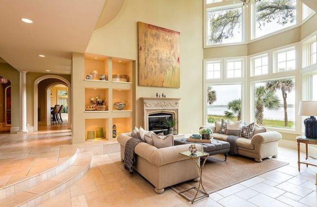 客廳有著高聳的天花板和落地窗、壁爐和吧台。(Realtor)