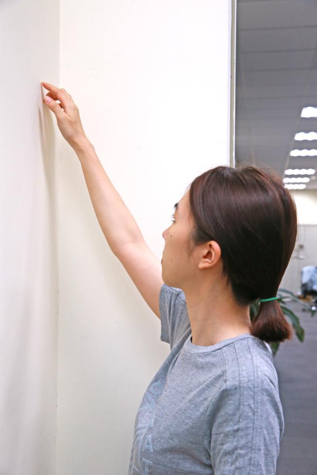 2.爬牆運動 面向牆壁站立,手指觸摸牆壁,慢慢向上爬行並逐漸伸直手臂,到不能向上為止。放鬆回原位,再重複動作。(記者陳柏亨/攝影)