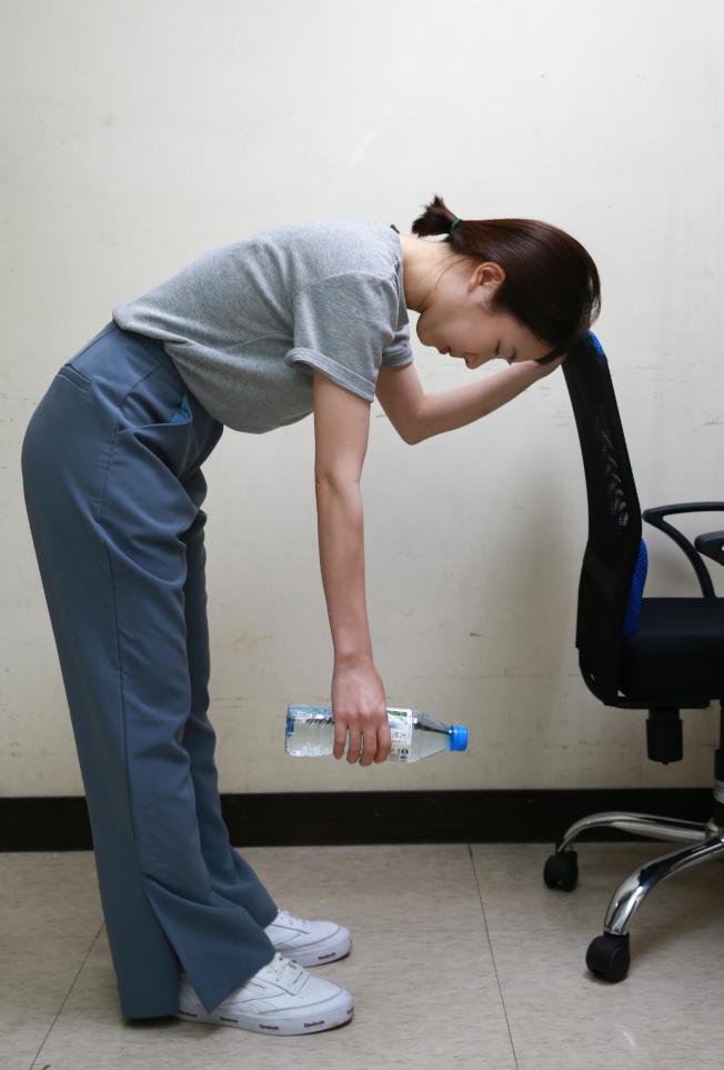 1.鐘擺運動 背部前傾,健側手臂扶住桌子或椅子,患側(五十肩手臂)下垂並握住啞鈴等重物,以患側肩膀為軸往前後、左右晃動。持重物的手要抓緊,但肩膀應放鬆,以達到牽引關節腔的目的。(記者陳柏亨/攝影)