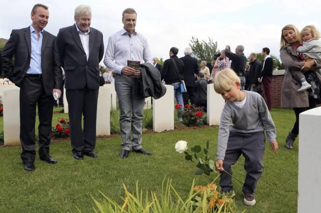 小男孩在一次世界大戰的烈士墓碑前獻花。(路透)