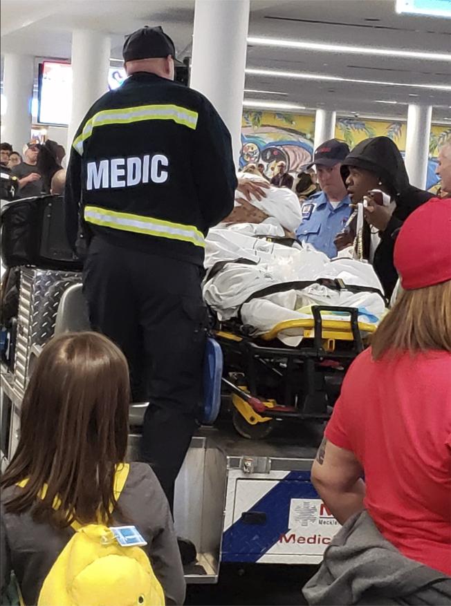 美國航空公司妮瑞妲‧阿勞荷在空橋上分娩後,接受緊急醫護人員的照顧。(美聯社)