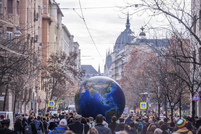 擔心失去地球自然環境的年輕學生上周走上街頭,要求政府正視地球暖化現象。圖為在匈牙利布達佩斯市的示威抗議場面,展示「只有一個地球」的主題。(美聯社)
