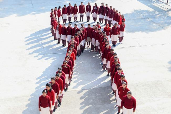紅絲帶像徵愛滋符號是源於1991年4月,紐約一個愛滋病小型慈善機構,用了此圖案,並命名為「看見愛滋」(Visual AIDS)。圖為印度阿姆力則的女學生排成紅絲帶圖案拍下照片。(Getty Images)