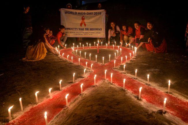 12月1日是世界愛滋日,從1988年開始,全球都有紀念愛滋的相關活動,圖為關注健康的組織WBVHA與性工作者將蠟燭排成紅絲帶的形狀並點燃。(Getty Images)