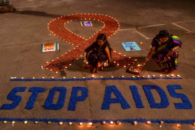 在印度也有民眾以燭光排出紅絲帶,並寫著終結愛滋(STOP AIDS)。(Getty Images)