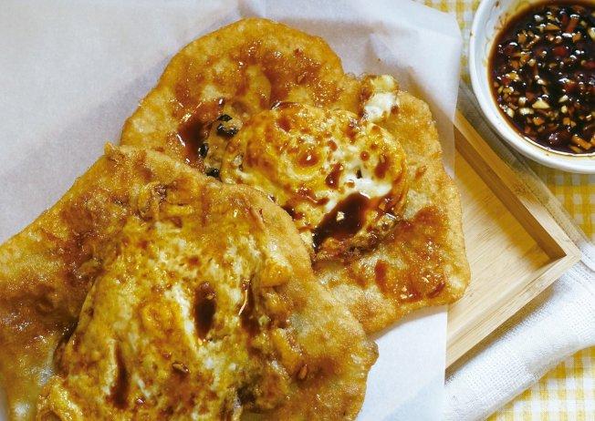 炸蛋蔥油餅刷上自調辣醬,摺起來吃特別美味。圖/太陽臉