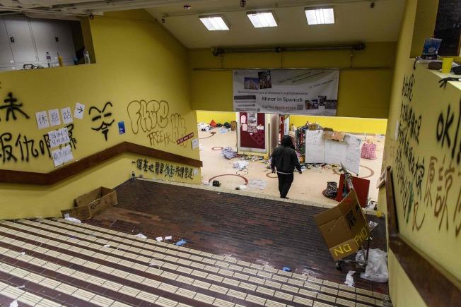 香港警方11月17日起封鎖理工大學校園,29日才撤離。圖為選擇留守的示威者Michael26日晚間正要去沖澡,牆上可見許多「反送中」相關塗鴉和文字。(Getty Imahes)