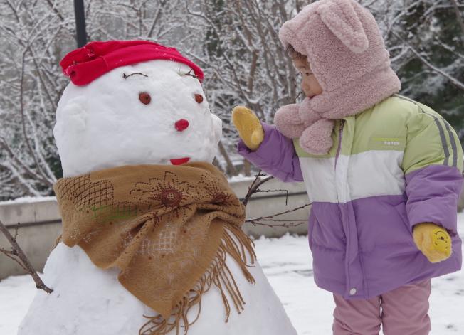 北京市從11月29日起出現降雪,圖為北京的小朋友被雪人吸引。(中新社)