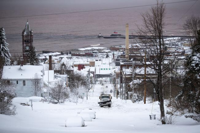 暴風雪襲明尼蘇達州,達魯斯的積雪近兩呎,圖為剷雪車在鏟除街道積雪。 (美聯社)