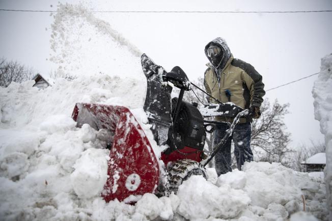 暴風雪襲明尼蘇達州,達魯斯的積雪近兩呎,居民全家動員鏟除家門前車道的積雪。 (美聯社)