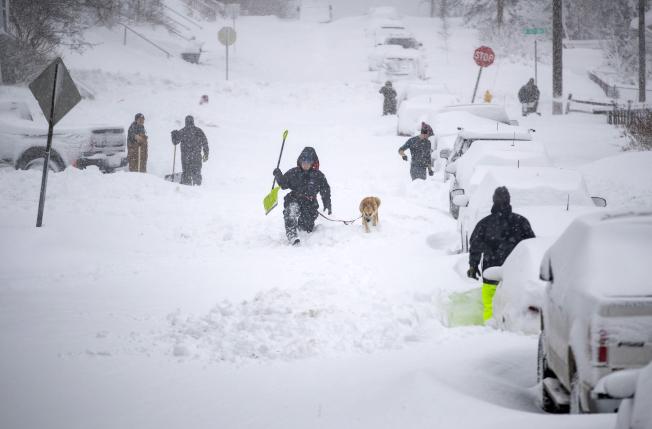 暴風雪襲明尼蘇達州,達魯斯的積雪近兩呎,居民大動員鏟除街道積雪。(美聯社)