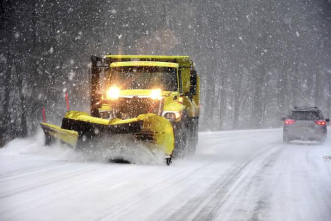 暴風雪來襲,30州交通大亂。圖為剷雪車在麻州7號公路剷除積雪。 (美聯社)