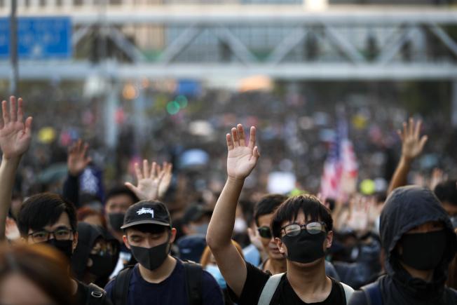 成千上萬香港市民1日發起尖沙咀到紅磡體育館的「毋忘初心大遊行」,出席者伸出五指,要求「五大訴求,缺一不可」。(美聯社)