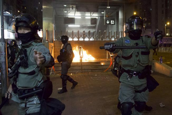 成千上萬香港市民1日發起尖沙咀到紅磡體育館的「毋忘初心大遊行」,最後演變成警民衝突。圖為港警在清理示威者在地鐵黃埔站投擲的汽油彈現場。(美聯社)