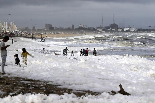 印度坦米爾那都省首府清奈著名的馬利納海灘(Marina Beach)今天連續第4天被白色泡沫覆蓋,造成印度新一波污染危機。圖為孩子們在海灘上的白色泡沫堆裡玩耍。美聯社