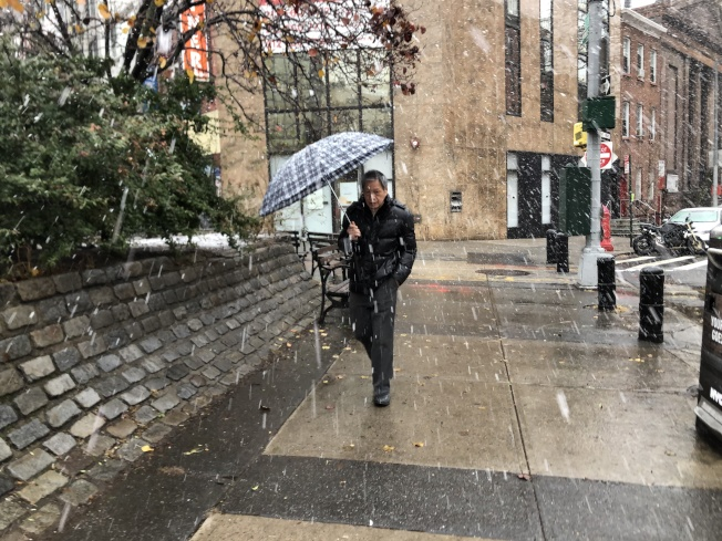 紐約市風雪在下午明顯增強,路上行人撐著傘抵風擋雪前行。(記者顏嘉瑩/攝影)
