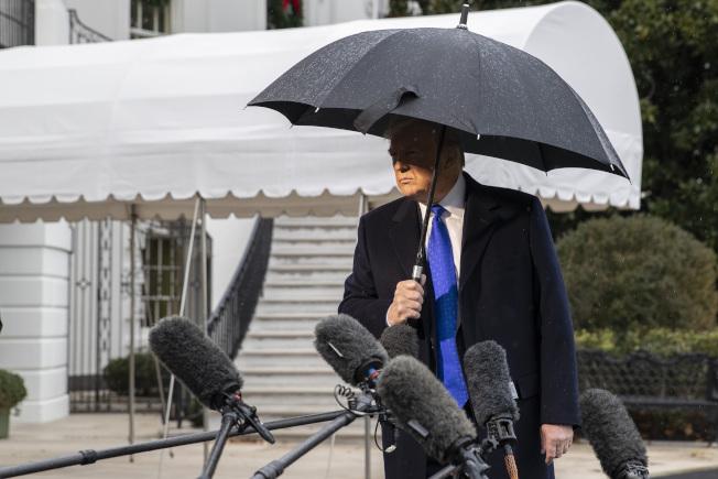 天空下著雨。美國總統川普2日由白宮出發前往倫敦參加北約峰會時,與媒體記者談話。(美聯社)