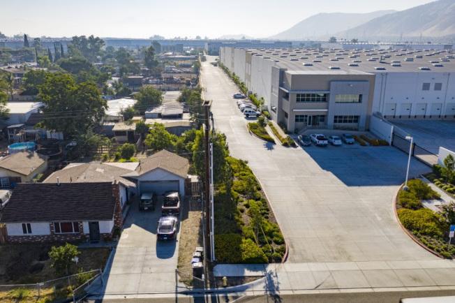 河濱縣與聖伯納汀諾縣無視居民健康,近年狂建倉庫,造成空污、噪音與交通壅塞,嚴重危及民眾生活品質,圖為芳塔那市(Fontana)的倉庫,與住家僅一街之隔。(洛杉磯時報)