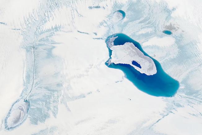 科學家觀察到格陵蘭冰蓋融化形成的湖泊快速乾涸。圖為格陵蘭冰蓋融化的衛星照片。(歐新社)