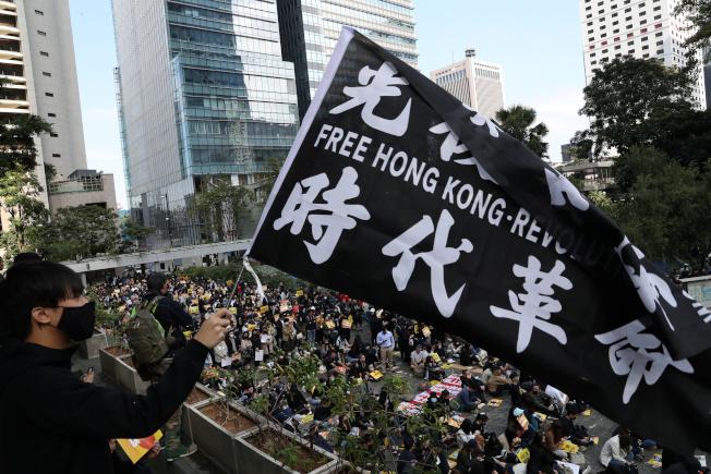香港民眾2日繼續在香港各區發起「和你Lunch」行動,有人揮動寫有「光復香港,時代革命」的旗幟。(路透)