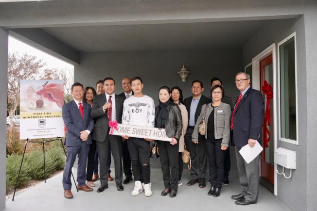 阿市市長Ross J. Maza(前排左二)將新屋鑰匙交給阿市華裔居民Yi Pang(前排左三)與他的母親張春芝(前排左四)。(記者陳開/攝影)