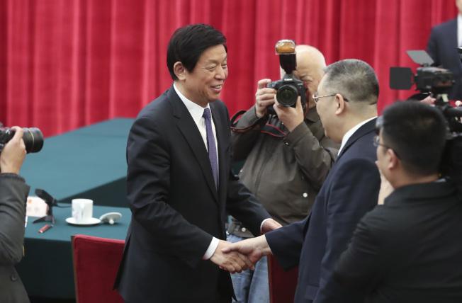 北京3日舉行「紀念澳門基本法實施20周年座談會」,圖為栗戰書(左)會後與崔世安握手。(中新社)
