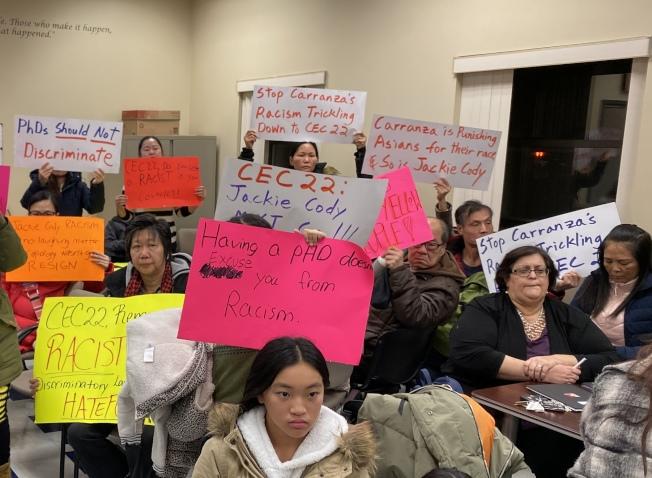華裔家長在第22學區教育理事會開會現場高舉抗議牌。(記者黃伊奕/攝影)