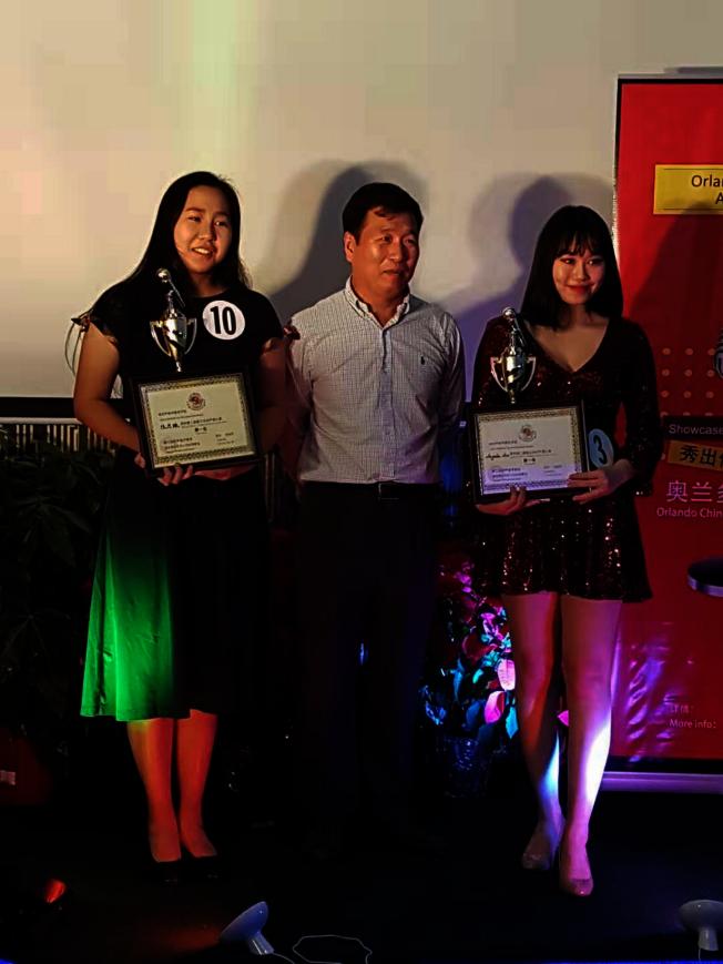奧蘭多華協會長邊發傑(中)為第二屆奧蘭多好聲音並列第一名的陳思緣(左)與Angela Luo(右)頒獎。(邊發傑提供)