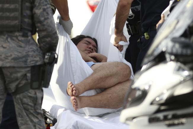槍案發生後,一名身分不明者被抬出基地。(美聯社)