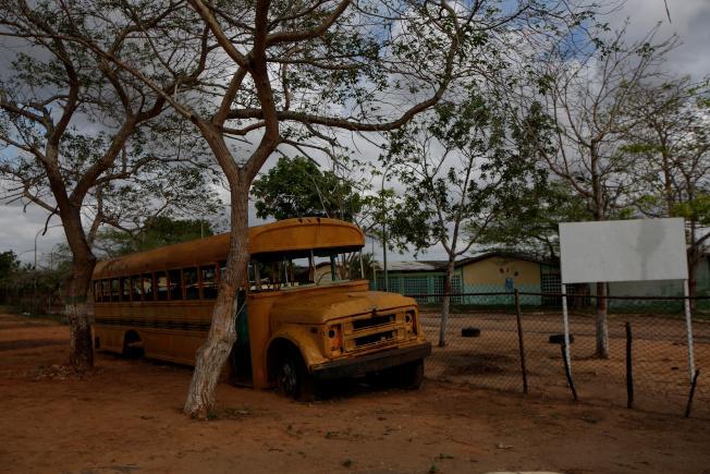委內瑞拉埃爾蒂格雷市郊一所關閉的學校,廢棄的校車還停在校外。路透