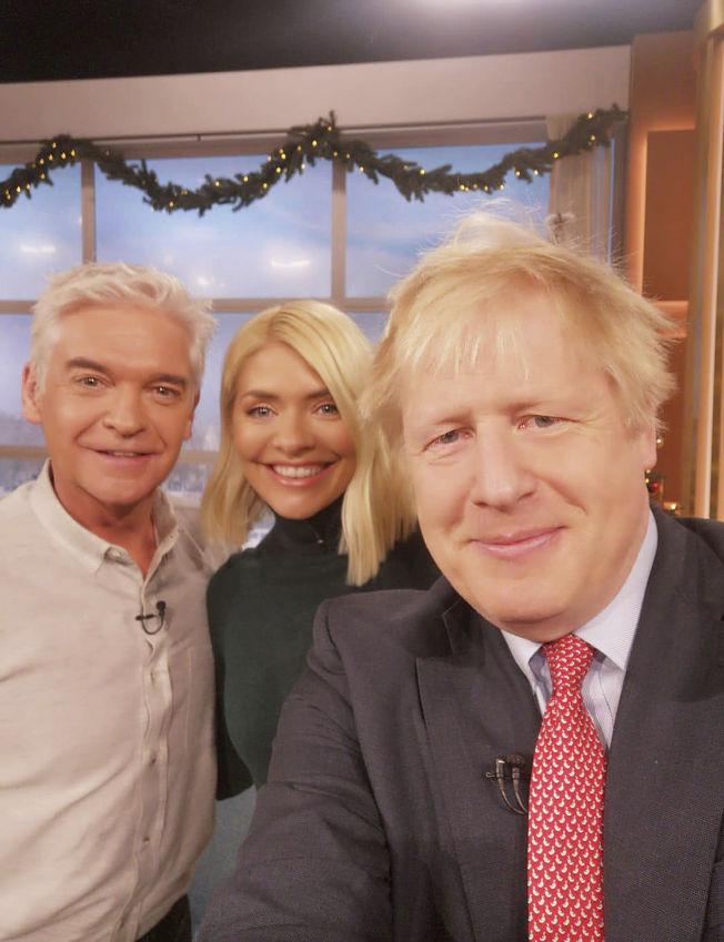 英國首相強生(右)自拍時使用的顯然是華為智慧手機。美聯社