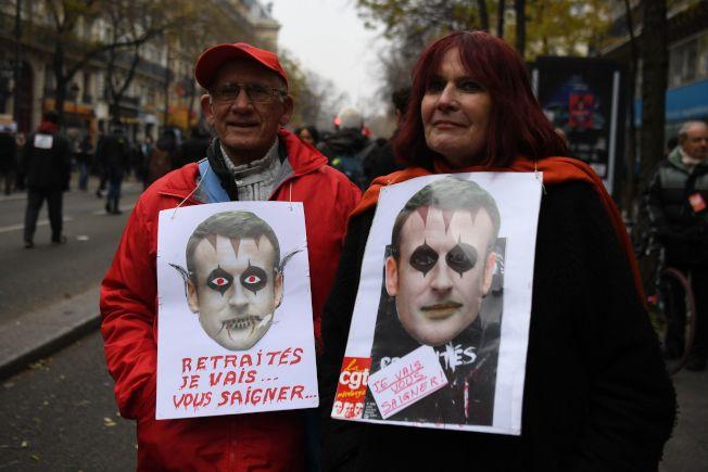 在巴黎的示威者持著被繪成是吸血鬼的馬克宏總統,「要榨乾你(工人)血」的標語,反對政府修改退休年金。(Getty Images)