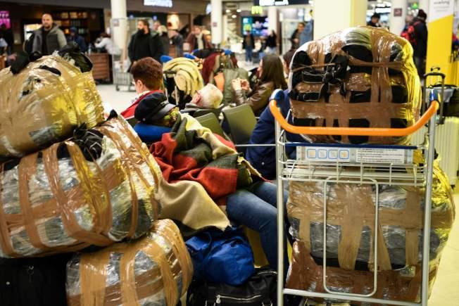 由於貧富不均導到法國政府修改退休年金引發的交通運輸無限期大罷工,正在法國各地展開。圖為5日在巴黎機場的旅客正在擔心航班是否能按時起飛。(Getty Images)
