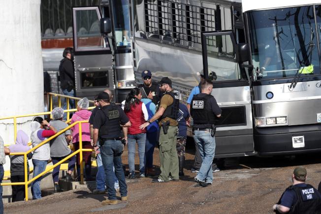 資料顯示,川普政府時期的移民執法部門進行的職場移民檢查比歐巴馬政府時期增加四倍。圖為今年8月在密西西比州食品廠進行移民突檢,多名工人被戴上手銬押上巴士。(美聯社)
