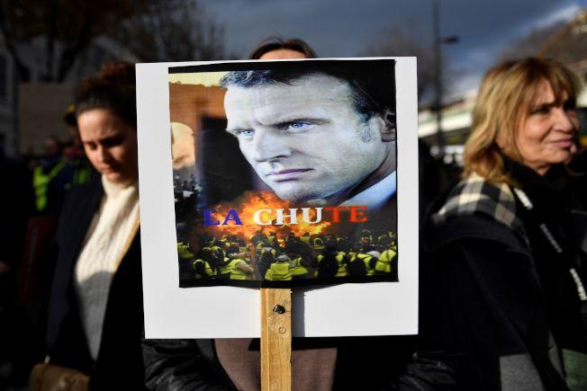 一名抗議者舉著法國總統馬克宏的肖像上寫著「下台」,抗議休改年金。(Getty Images)