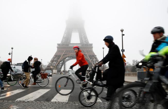 巴黎知名觀光景點艾菲爾鐵塔5日同樣因罷工關閉。大批自行車騎士經過巴黎鐵塔。法國正遭遇全國運輸大罷工。(路透)