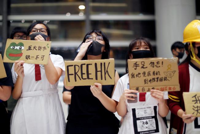 香港立法會6日通過議案,要求教育局追究煽動仇恨言論或慫恿學生參與非法集會的老師。圖為戴著口罩的香港中學生9月23日手持標語,響應反送中抗爭。(路透)