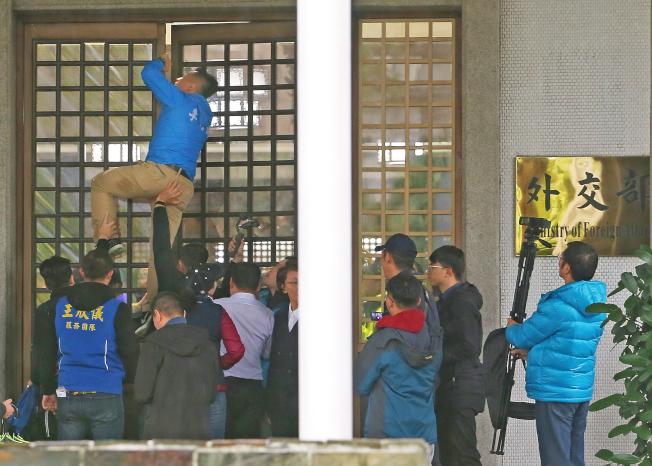 國民黨立院團立委與台北市議員到外交部抗議,外交部關閉大門不讓議員與媒體進入,台北市議員李明賢企圖爬縫隙進入。(記者余承翰/攝影)