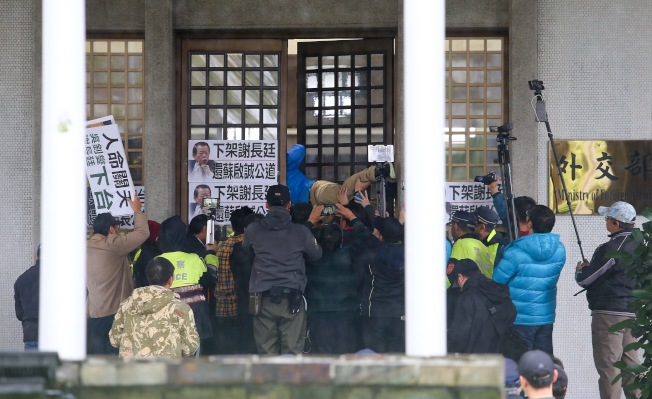 「卡神」楊蕙如涉網軍事件延燒,國民黨立委與市議員6日至外交部抗議,被擋在門口不得進入,台北市議員李明賢企圖從縫隙爬進去。(記者余承翰/攝影)