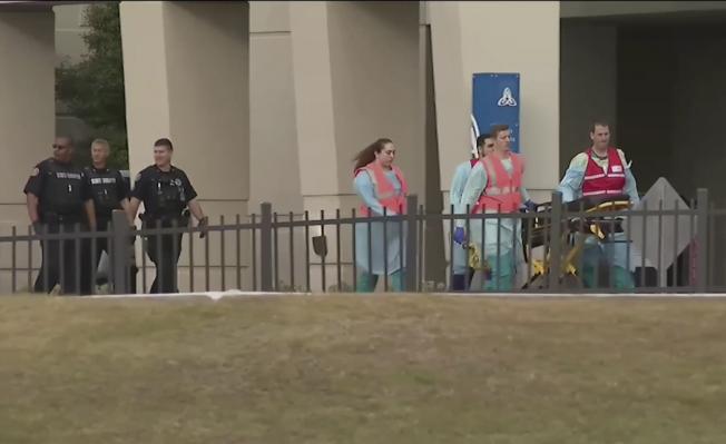 佛州海軍航空基地爆發槍案,醫護人員緊急將受傷者送往醫院。(美聯社)