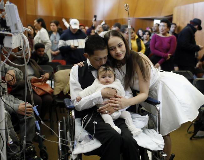 哈維爾·羅德里格斯和高中戀人,在芝加哥醫院的小教堂成婚,二人懷中是今年初出生的女兒。(美聯社)
