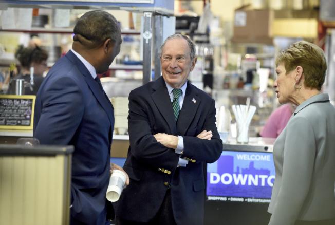 民主黨總統參選人彭博 (中)和喬州奧斯古市市長 (左)在咖啡館與一名婦女聊天。(美聯社)