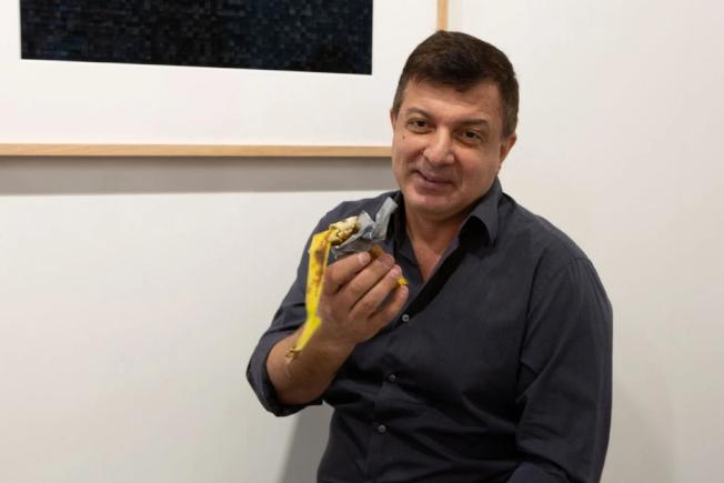 紐約行為藝術家達圖那拿著剩下的半根香蕉。(路透)
