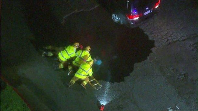 消防員向天坑探頭,旁邊一輛廂型車後輪被卡住懸掛在天坑邊緣。(KTLA電視台)