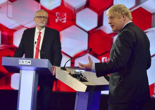 英國首相暨保守黨黨魁強生(右)和工黨黨魁柯賓(J左)6日進行大選前最後一次一對一辯論。(美聯社)